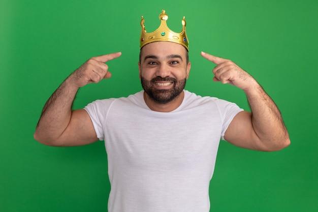 Bärtiger mann im weißen t-shirt, das glückliches und fröhliches lächeln der goldenen krone trägt und mit zeigefingern auf seine krone zeigt, die über grüner wand steht