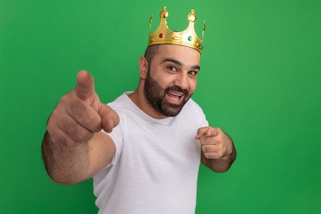 Bärtiger mann im weißen t-shirt, das glückliches und positives zeigen der goldenen krone mit zeigefingern trägt, die über grüner wand stehen