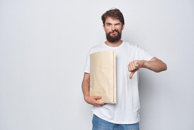 Bärtiger mann im weißen t-shirt kraftbeutel-einkaufspaket. foto in hoher qualität