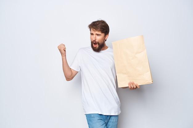 Bärtiger mann im weißen t-shirt kraftbeutel einkaufspaket