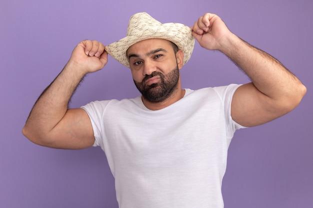 Bärtiger mann im weißen t-shirt und im sommerhut mit dem selbstbewussten ausdruck, der seinen hut berührt, der über lila wand steht