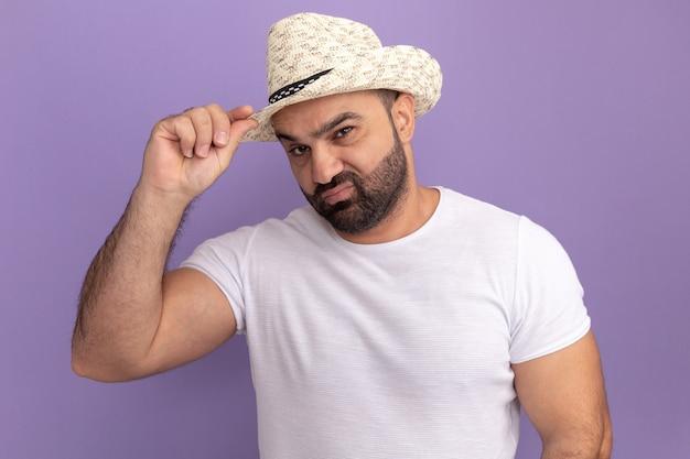 Bärtiger mann im weißen t-shirt und im sommerhut mit skeptischem ausdruck, der seinen hut berührt, der über lila wand steht