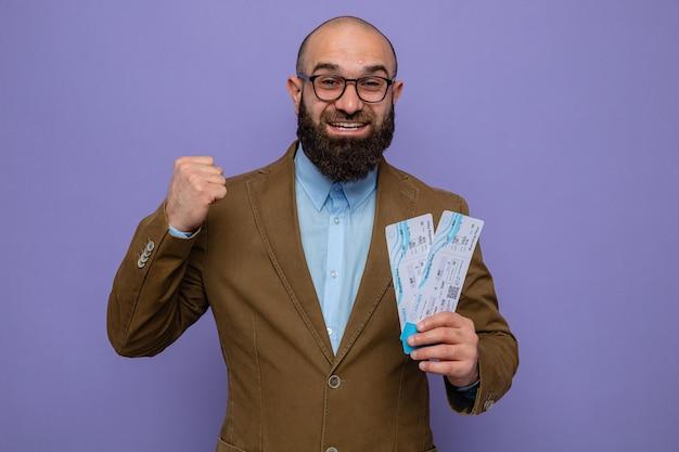 Bärtiger mann in braunem anzug mit brille, der flugtickets glücklich und aufgeregt mit geballter faust hält, freut sich über seinen erfolg auf violettem hintergrund