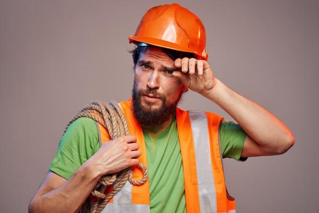 Bärtiger mann in der bauuniform des berufs der harten arbeit
