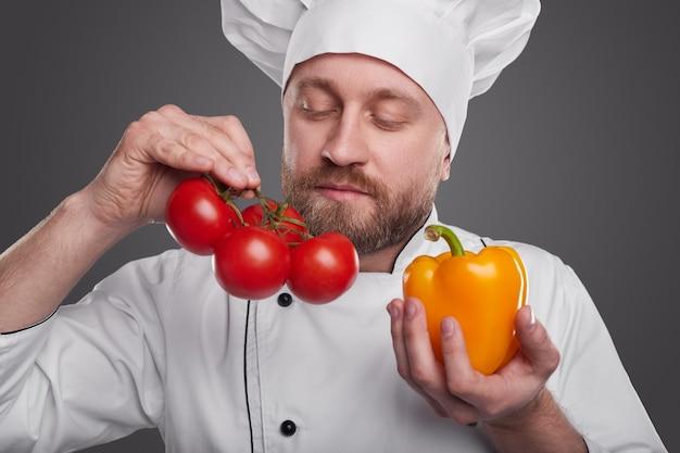 Bärtiger mann in der kochuniform, die reife tomaten und pfeffer während der arbeit im restaurant gegen grauen hintergrund schnüffelt