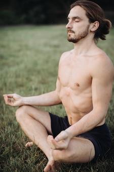 Bärtiger mann in der lotoshaltung, die auf grünem gras sitzt, konzept der ruhe und der meditation,