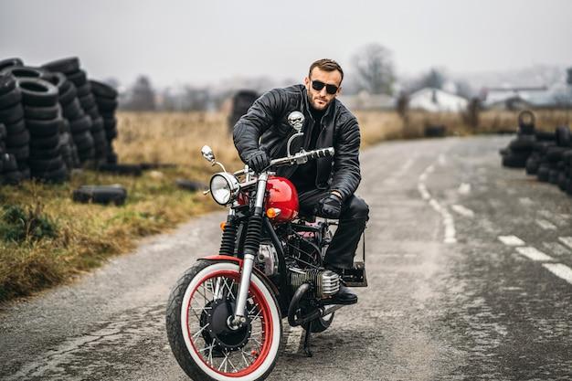 Bärtiger mann in der sonnenbrille und in lederjacke, welche die kamera beim sitzen auf einem motorrad auf der straße betrachten. hinter ihm ist eine reihe von reifen
