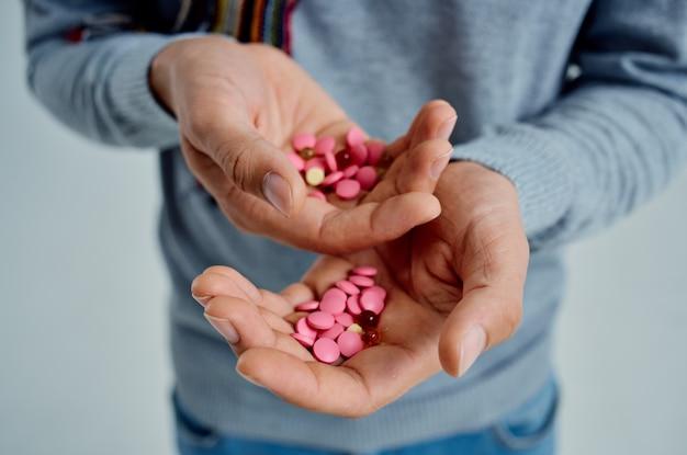 Bärtiger mann in einem pullover mit pillen in der hand gesundheitsprobleme isolierter hintergrund