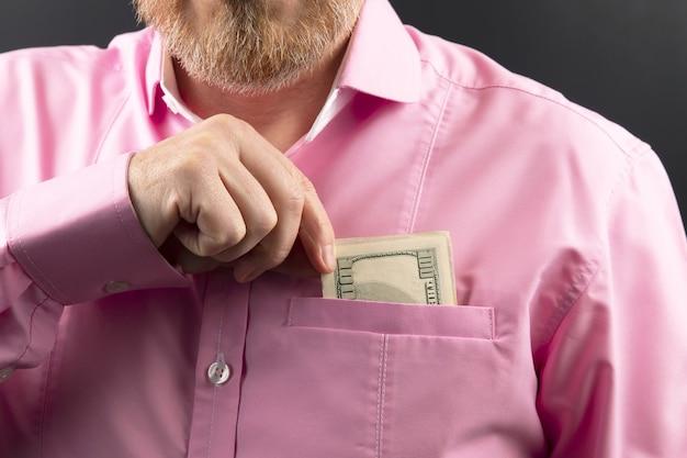 Bärtiger mann in einem rosa hemd versteckt geld in seiner tasche