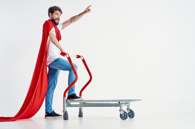 Bärtiger mann in einem roten manteltransport in einem hellen hintergrund der kiste