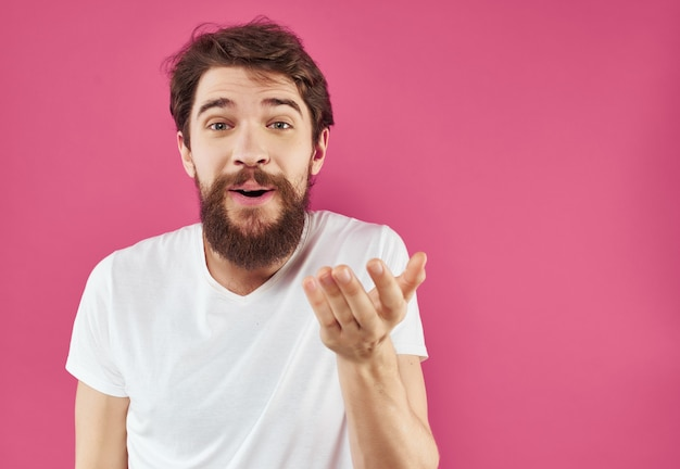 Bärtiger mann in einem weißen t-shirt glücklicher gesichtsausdruck studio. foto in hoher qualität