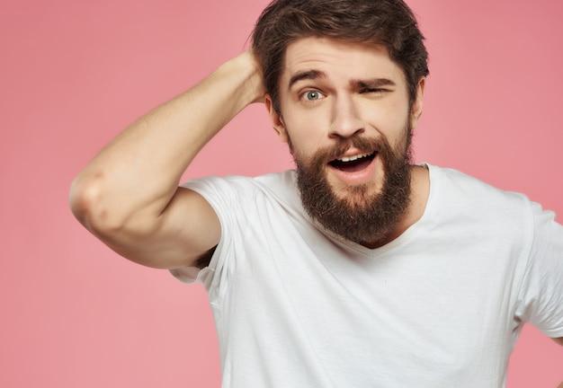 Bärtiger mann in einem weißen t-shirt handgesten wut studio. foto in hoher qualität