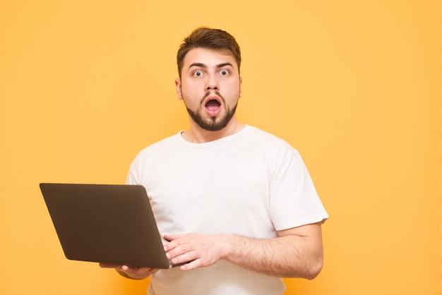 Bärtiger mann in einem weißen t-shirt mit einem laptop in seinen händen ist auf einem gelben isoliert