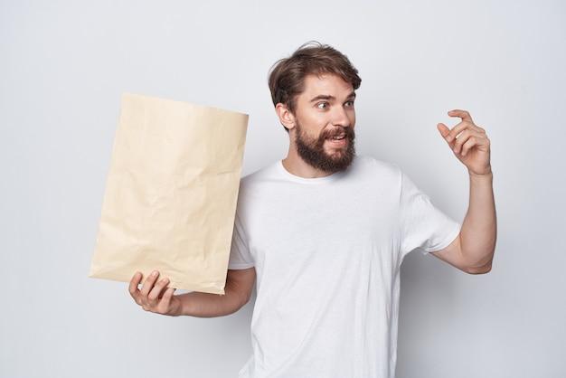 Bärtiger mann in einem weißen t-shirt mit einem paket in den händen emotionsmodell