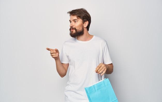 Bärtiger mann in einem weißen t-shirt mit einem paket in seiner hand einkaufsspaß isoliert.