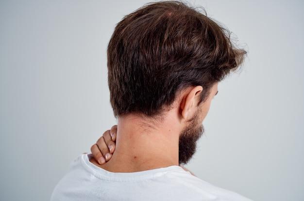 Bärtiger mann in einem weißen t-shirt stress-medizin-schmerz in der nackenstudio-behandlung