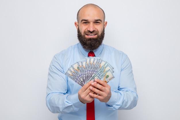 Bärtiger mann in roter krawatte und blauem hemd, der bargeld hält, der glücklich und zufrieden aussieht und fröhlich lächelt