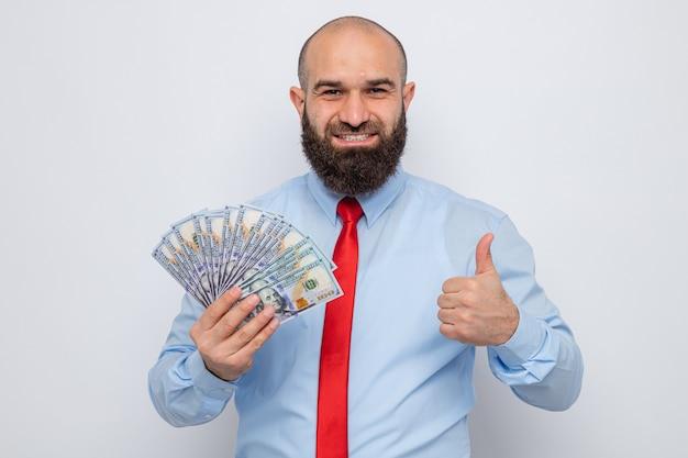 Bärtiger mann in roter krawatte und blauem hemd, der bargeld hält und fröhlich lächelt und daumen nach oben zeigt