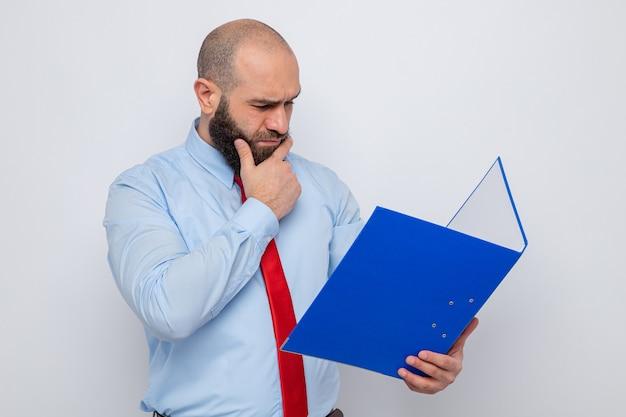 Bärtiger mann in roter krawatte und blauem hemd, der einen büroordner hält und ihn verwirrt auf weißem hintergrund betrachtet