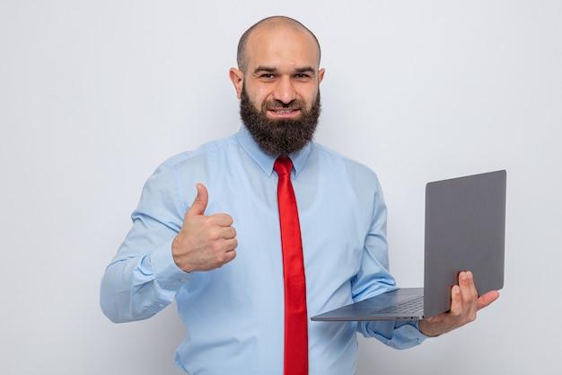 Bärtiger mann in roter krawatte und blauem hemd, der einen laptop hält und in die kamera schaut, lächelt fröhlich und zeigt daumen hoch stehend auf weißem hintergrund