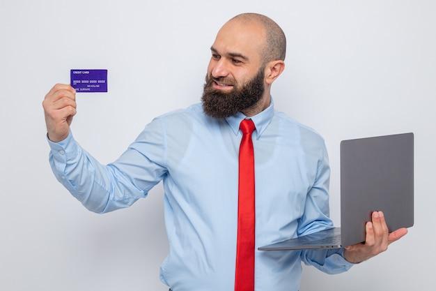 Bärtiger mann in roter krawatte und blauem hemd, der laptop und kreditkarte hält und es glücklich und zufrieden auf weißem hintergrund betrachtet