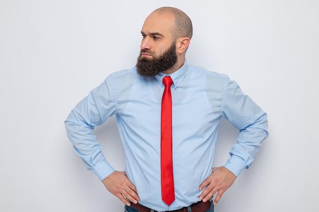 Bärtiger mann in roter krawatte und blauem hemd, der mit ernstem gesicht mit den händen an der hüfte beiseite schaut