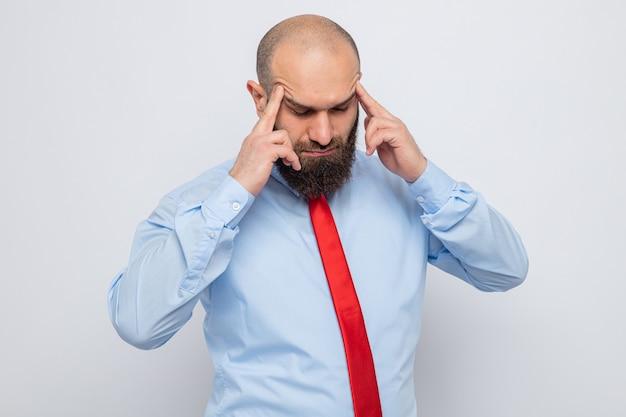 Bärtiger mann in roter krawatte und blauem hemd, der seine schläfen mit den fingern berührt, die sich unwohl fühlen und unter kopfschmerzen leiden