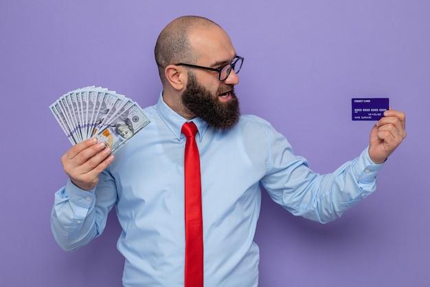 Bärtiger mann in roter krawatte und blauem hemd mit brille, der bargeld und kreditkarte hält und es mit einem lächeln im gesicht betrachtet, das glücklich und positiv auf violettem hintergrund steht standing