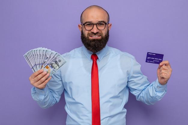 Bärtiger mann in roter krawatte und blauem hemd mit brille, der bargeld und kreditkarte hält und selbstbewusst lächelt