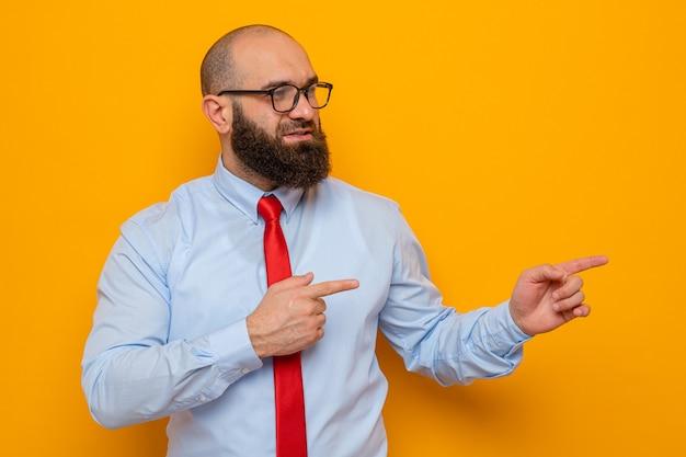 Bärtiger mann in roter krawatte und blauem hemd mit brille, der beiseite lächelt und mit den zeigefingern zur seite zeigt
