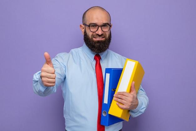 Bärtiger mann in roter krawatte und blauem hemd mit brille, der büroordner hält und fröhlich lächelt und daumen nach oben zeigt
