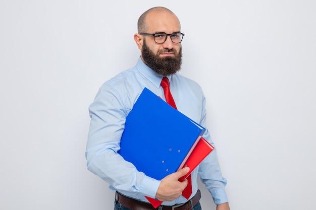Bärtiger mann in roter krawatte und blauem hemd mit brille, der büroordner hält und in die kamera schaut, mit ernstem, selbstbewusstem ausdruck auf weißem hintergrund