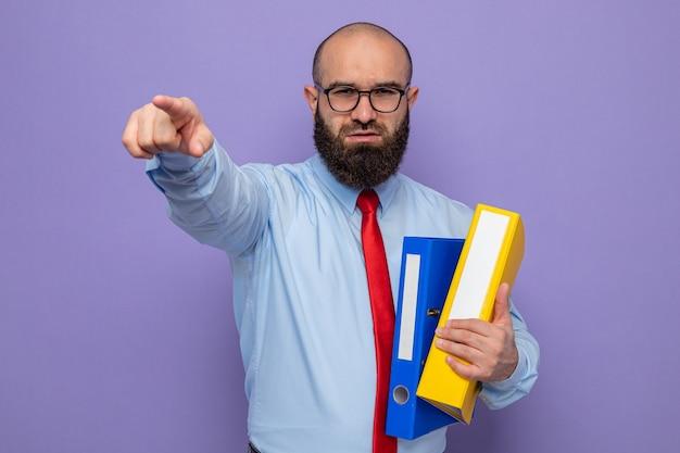 Bärtiger mann in roter krawatte und blauem hemd mit brille, der büroordner hält und mit selbstbewusstem ausdruck in die kamera schaut, der mit dem zeigefinger auf die kamera zeigt, die über violettem hintergrund steht