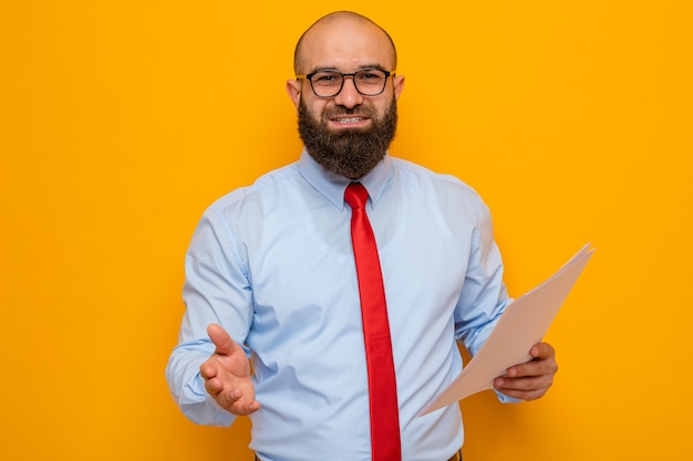 Bärtiger mann in roter krawatte und blauem hemd mit brille, der dokumente hält und handgrüße anbietet