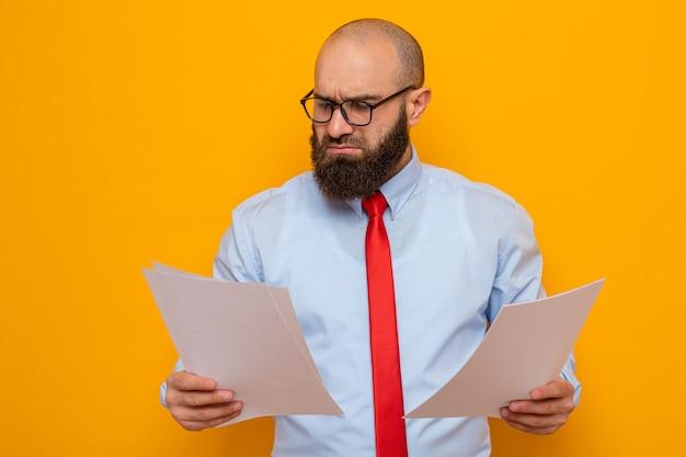 Bärtiger mann in roter krawatte und blauem hemd mit brille, der dokumente hält und sie mit ernstem gesicht betrachtet