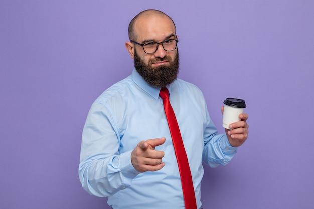 Bärtiger mann in roter krawatte und blauem hemd mit brille, der glücklich und positiv aussieht und eine kaffeetasse hält, die mit dem zeigefinger nach vorne zeigt