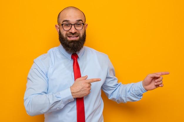 Bärtiger mann in roter krawatte und blauem hemd mit brille, der glücklich und überrascht in die kamera schaut und mit zeigefingern auf die seite zeigt, die über orangefarbenem hintergrund steht