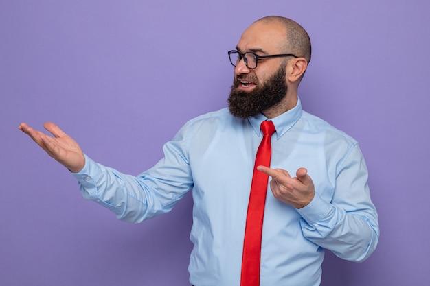 Bärtiger mann in roter krawatte und blauem hemd mit brille, der glücklich und zufrieden beiseite schaut und sich mit dem arm seiner hand präsentiert, der mit dem zeigefinger zur seite zeigt