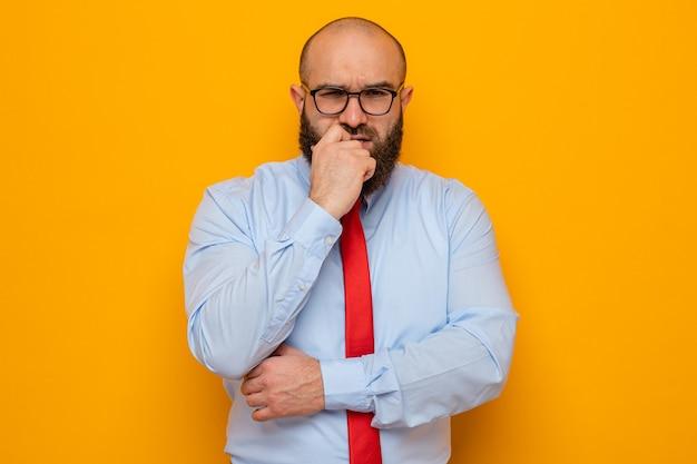 Bärtiger mann in roter krawatte und blauem hemd mit brille, der mit der hand am kinn in die kamera schaut und denkt, dass er über orangefarbenem hintergrund steht