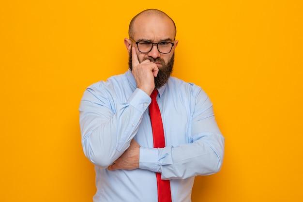 Bärtiger mann in roter krawatte und blauem hemd mit brille, der mit ernstem gesicht schaut und den finger auf seine wange denkt
