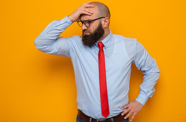 Bärtiger mann in roter krawatte und blauem hemd mit brille, der verwirrt beiseite schaut und die hand für einen fehler auf der stirn hält