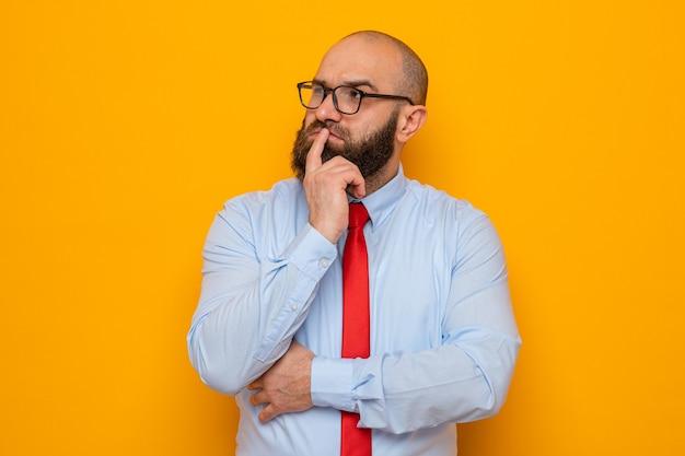 Bärtiger mann in roter krawatte und blauem hemd mit brille, der verwirrt beiseite schaut
