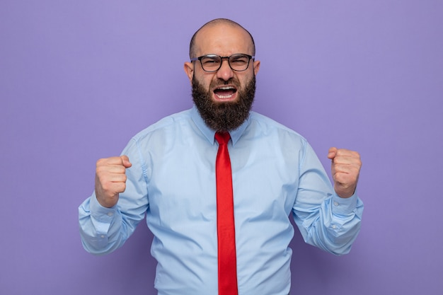Bärtiger mann in roter krawatte und blauem hemd mit brille, der wütend und aufgeregt mit geballten fäusten aussieht