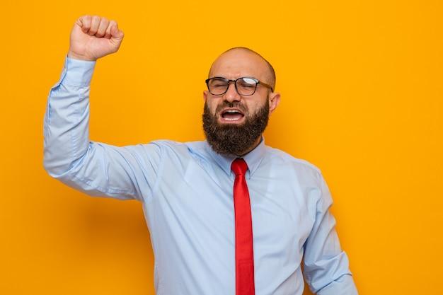 Bärtiger mann in roter krawatte und blauem hemd mit brille, glücklich und aufgeregt, geballte faust