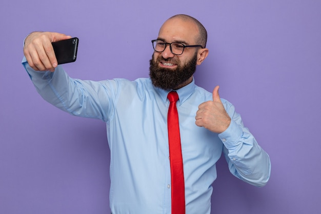 Bärtiger mann in roter krawatte und blauem hemd mit brille macht selfie mit smartphone und lächelt fröhlich und zeigt daumen hoch