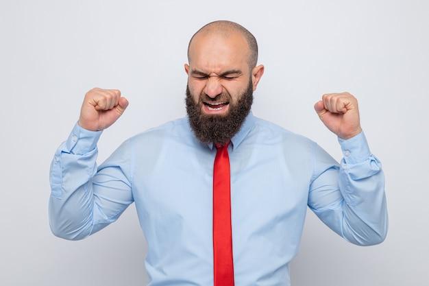 Bärtiger mann in roter krawatte und blauem hemd schreit und schreit verrückt, wütend und frustriert, fäuste hebend