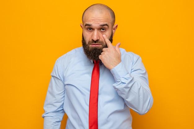 Bärtiger mann in roter krawatte und hemd, der mit dem zeigefinger auf sein auge zeigt, das über orangefarbenem hintergrund steht
