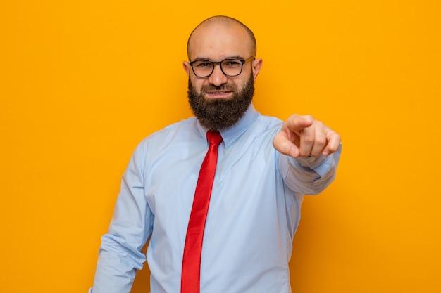 Bärtiger mann in roter krawatte und hemd mit brille, der glücklich aussieht und mit dem zeigefinger nach vorne zeigt