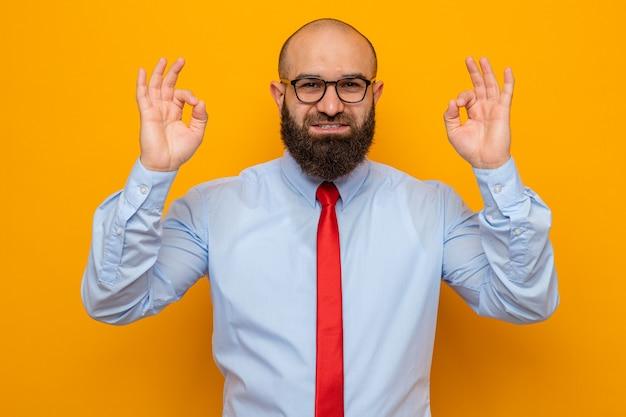 Bärtiger mann in roter krawatte und hemd mit brille, der glücklich und fröhlich aussieht und ein gutes zeichen zeigt