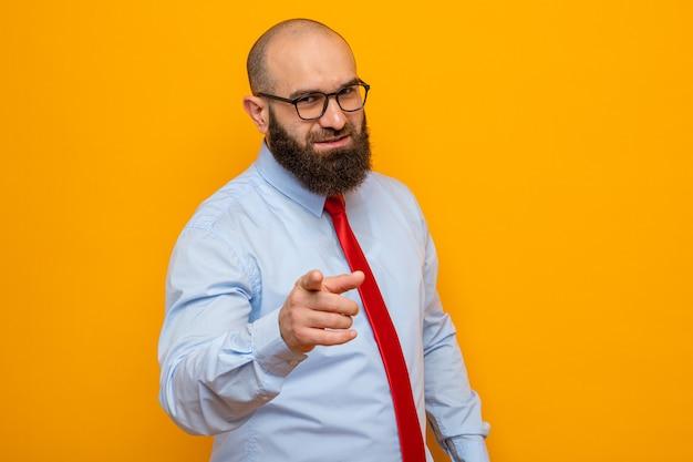Bärtiger mann in roter krawatte und hemd mit brille, der mit dem zeigefinger nach vorne zeigt und fröhlich lächelt